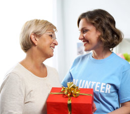 a volunteer giving gift to a senior woman