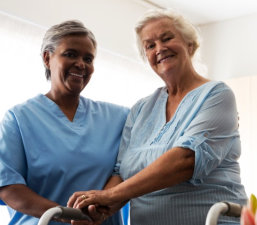 caregiver helping senior woman walk with walker