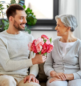 man giving flowers to a senior woman