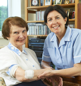Nurse and elderly woman smiling looking in to camera