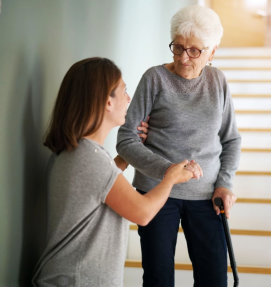 caregiver helping senior woman get down from stairs