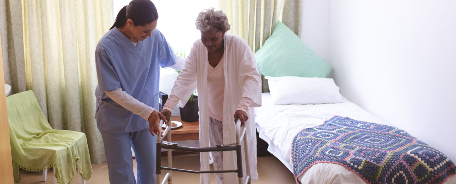 Front view of mixed race female nurse helping senior mixed race female patient to stand with walker at nursing home