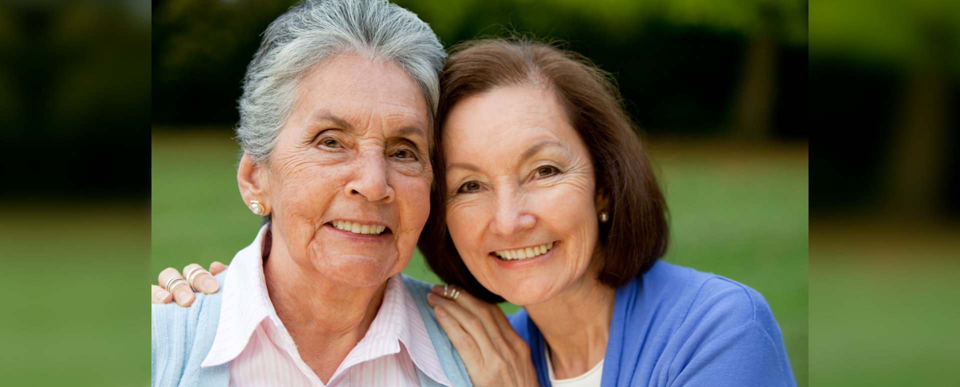 Portrait of an elder mother and daughter smiling outdoors