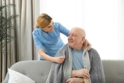 caregiver giving a blanket to a senior man