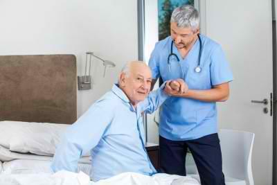 nurse helping senior man get up