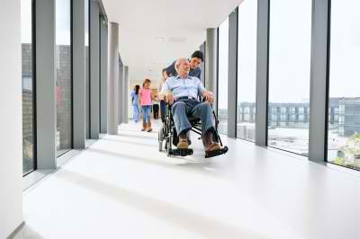 happy nurse and senior man on a wheelchair