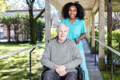nurse accompanying a senior man on wheelchair